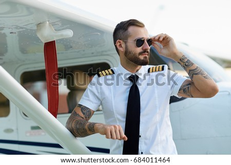 0004dc68534 Cool young adult pilot with tattoos in sunglasses posing at private motor  airplane on runway near
