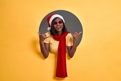 Cool young African woman in Santa Claus hat, red scarf and sunglasses doing phone gesture call me back with hand and fingers like talking on the telephone in a circle hole in a yellow wall. Copy space