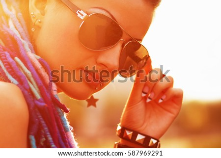 Cool young freaky girl in sunglasses posing.Fashionable chick with braided blue hair,lip piercing on face.Closeup portrait of teen street fashion model.Freak model in bright orange sunset light #587969291