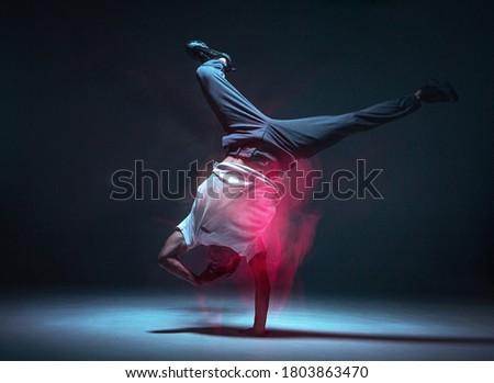 Cool young guy breakdancer dancing hip-hop in neon light. Dance school poster. Long exposure shot Photo stock ©