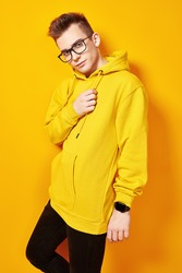Cool young man in bright yellow hoody and glasses posing on a yellow background. Youth fashion.