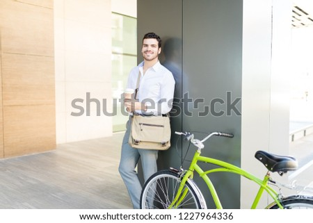Cool young man in formals with coffee cup and cycle smiling in the corridor #1227964336
