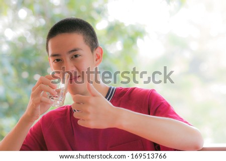 cool young man in red t-shirt holding a glass of water with thump up