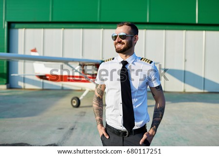 880484958c3 Cool young pilot in sunglasses posing at private motor airplane on runway  near hangar.