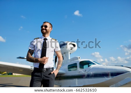 60264530766 ... motor airplane on runway near hangar. Cool young pilot in sunglasses  with tattoos on his hands posing at private air plane on