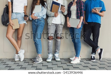 Cool youth time. Teenagers standing at campus wall, holding devices and books, panorama with free space #1413936446