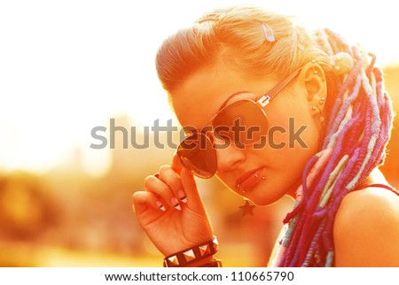 Coolest young chick posing at sunset.Punk teenage braided white girl posing in sunglasses.Portrait of punky cool teen girl.Fashionable female model with braids,lip piercing,nail work.Teenager fashion - stock photo