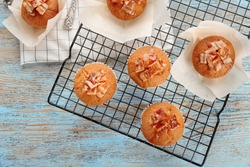Cooling rack with tasty bacon muffins on table