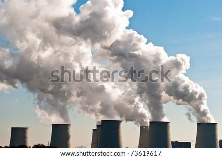 Cooling towers of a power plant with steam clouds and sky