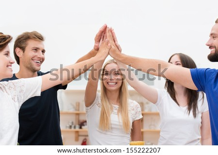 Cooperation and agreement - a group of happy laughing young multicultural friends stand in a circle placing their raised hands together in the centre as a team effort