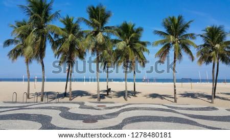 Copacabana Beach Rio de Janeiro boardwalk with palm trees and bl