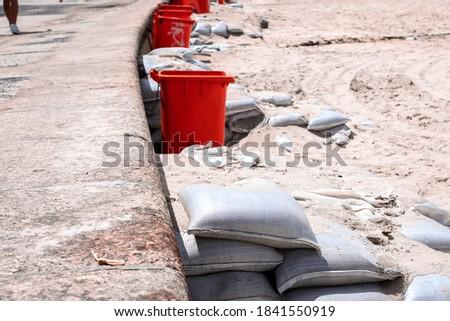 Copacabana beach sidewalk with sandbags as stair steps and orange waste bins Foto stock ©