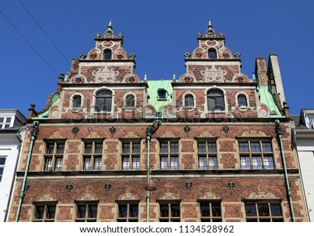 Copenhagen, Denmark - facades in Dutch Renaissance style of a building  in city center  with the green copper roof cover characteristic of the city profile