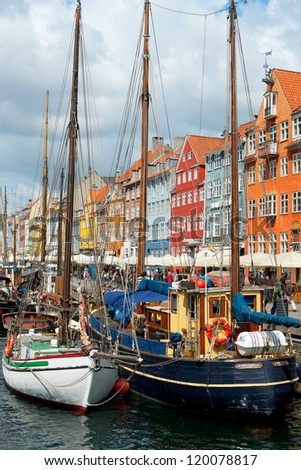 COPENHAGEN, DENMARK - JUNE 1: Boats at the harbor in Nyhavn against multicolored houses on June 1, 2012 in Copenhagen. Nyhavn is a 17th century embankment, canal and entertainment area in Copenhagen.