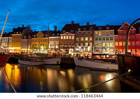 COPENHAGEN, DENMARK - JUNE 1: Boats at the harbor in Nyhavn at night against cafes on June 1, 2012 in Copenhagen. Nyhavn is a 17th century embankment, canal and entertainment area in Copenhagen.