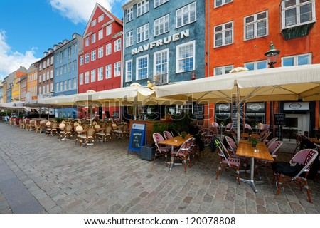 COPENHAGEN, DENMARK - JUNE 1: Houses with small cafes on Nyhavn on June 1, 2012 in Copenhagen. Nyhavn is a 17th century embankment, canal and entertainment area in Copenhagen. - stock photo