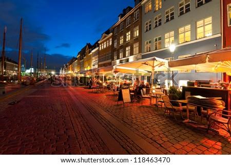 COPENHAGEN, DENMARK - JUNE 1: Small cafes on Nyhavn at night on June 1, 2012 in Copenhagen. Nyhavn is a 17th century embankment, canal and entertainment area in Copenhagen.