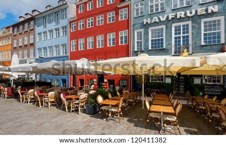 COPENHAGEN, DENMARK - JUNE 1: Small cafes on Nyhavn in the morning on June 1, 2012 in Copenhagen. Nyhavn is a 17th century embankment, canal and entertainment area in Copenhagen.