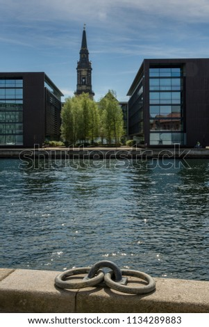 Copenhagen, Denmark - June 9 2018 : View of Christians Kirke, Christians Church, sandwiched between the modern buildings lining the waterway in the historic district of Christianshavn in Copenhagen