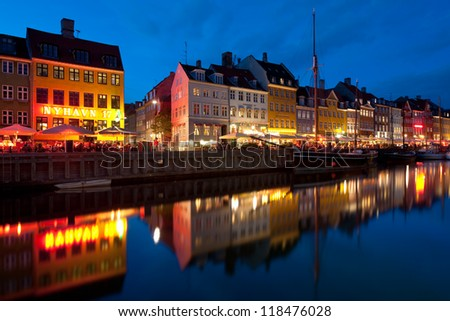 COPENHAGEN, DENMARK - MAY 31: Old buildings and cafes in Nyhavn at night on May 31, 2012 in Copenhagen. Nyhavn is a 17th century embankment, canal and entertainment area in Copenhagen.