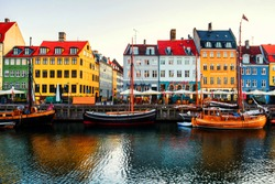 Copenhagen, Denmark. View of famous Nyhavn area in the center of Copenhagen, Denmark in the morning. Boats moored with historical buildings, clear bright sky