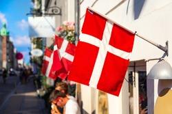 Copenhagen iconic view. Denmark flags near Nyhavn canal on medieval houses in the center of Copenhagen, Denmark during summer sunny day