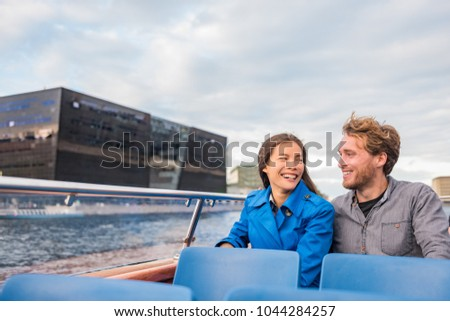 Copenhagen tourists couple on city boat cruise tour enjoying view of the black diamond Royal library, famous architecture building, Denmark, Europe travel. People traveling.