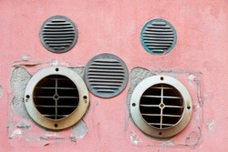 Copper and plastic ventilation grilles against an old and damaged plaster wall.