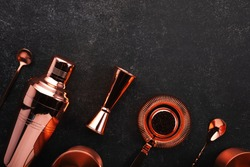 Copper bar tools and accessories for making cocktail. Shaker, jigger, strainer, spoon. Alcohol drinks and beverages preparation concept. Black background, top view, copy space