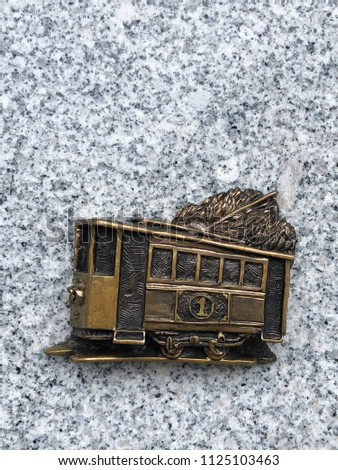 copper bas-relief depicting an old tram. Vintage tram on the stone background #1125103463