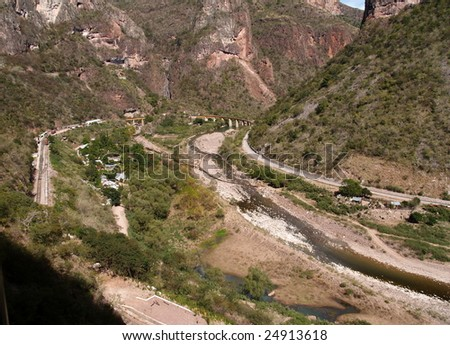 Copper Canyon railway winds its way into the interior of Mexico over a curving bridge  seen here from the third of three levels of train track