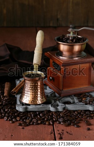 copper coffee pot with beans on a wooden table #171384059