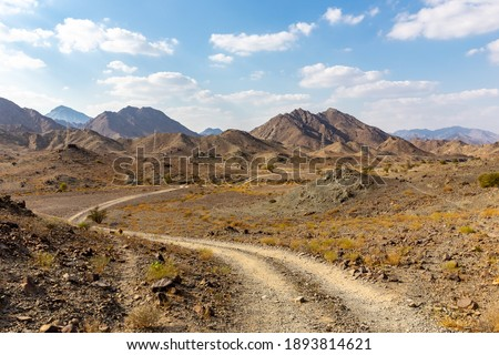 Copper Hike trail, winding gravel dirt road through Wadi Ghargur riverbed and rocky limestone Hajar Mountains in Hatta, United Arab Emirates.  Foto stock ©