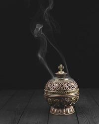 Copper incense holder on dark wooden background bukhoor burner white smoke