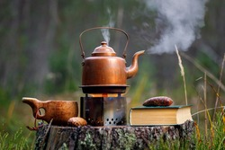Copper kettle on the stove with a book and a wooden cup on an old stump in the forest.