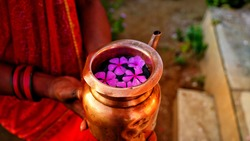 Copper mug in a human hand. Devotee mug full of water with fragrant pink flowers to worship god. Hindu devotee culture concept.