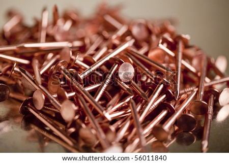 Copper Nails on Galvanized Steel Background With Shallow Focus