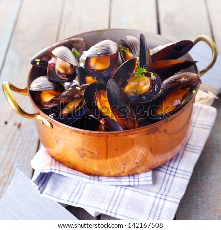 Copper pot of gourmet mussels served on a napkin garnished with fresh herbs for a tasty seafood meal - stock photo