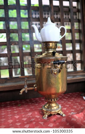 Copper samovar with white teapot in russian restaurant