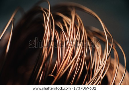 Copper scrap metal, wire, windings of motors and transformers, electrical wire without insulation. Against the background of a copper sheet. Close-up. Macro. Stockfoto ©