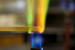 Copper solution burning on a wooden splint in a bunsen burner flame.