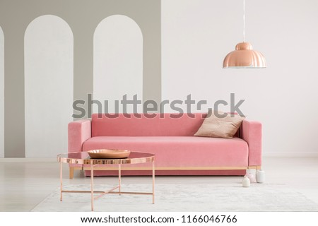 Copper table in front of pink sofa with cushion in white living room interior with lamp. Real photo