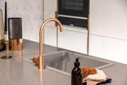 Copper tap in modern grey kitchen interior