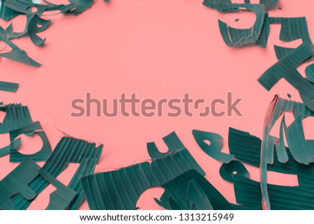 Copy space and frame from letters green tropical palm leaves on pink textured background. Original idea from natural material for summer design and needlework #1313215949