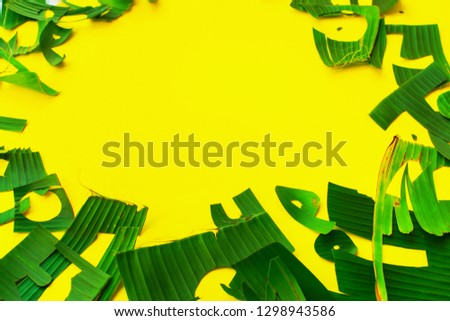 Copy space and frame from letters green tropical palm leaves on yellow textured background. Original idea from natural material for summer design and needlework #1298943586
