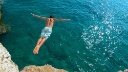 COPY SPACE: Athletic young man jumping off a rocky ledge and into the glistening blue ocean. Unrecognizable male tourist on a relaxing summer vacation in does cliff diving on a beautiful sunny day.