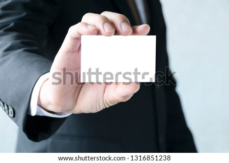Copy space concept.Businessman holding a white business card.Wearing a white tie shirt,Wearing a black suit,looking good and dignified.Free space to put letters or pictures to create advertising media