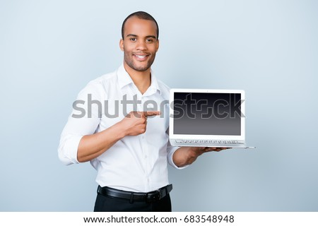 Copy space concept. Young handsome mulatto banker on the pure light blue background is pointing on a laptop`s monitor with his finger, wearing white strict shirt #683548948