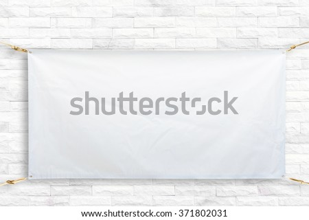 Copy space for text on disastrously white vinyl banner on white brick background .Clipping path horizontal .sign background #371802031