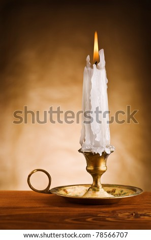 copy space image of ablaze candle in old candlestick